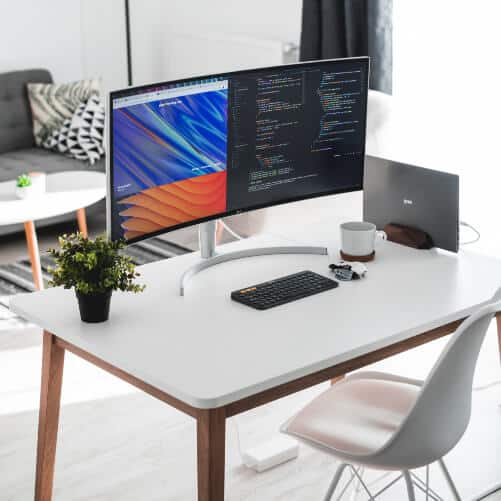 computer monitor and pot plant on a white desk
