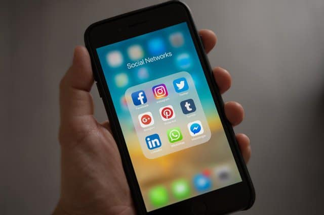 A man's hand holding a phone showing social media icons